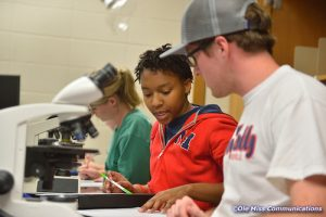 Two students are working together on a lab sheet in front a microscope in a biology lab